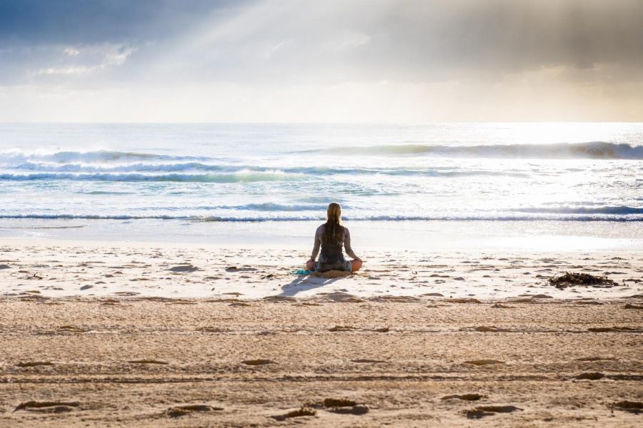 Photo of a person meditating at the beach.