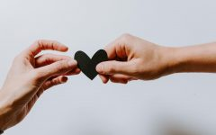 Two hands reaching out to hold a heart together.